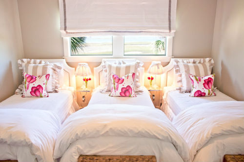 Three Beds Plus White Coverletts and Floral Pillows